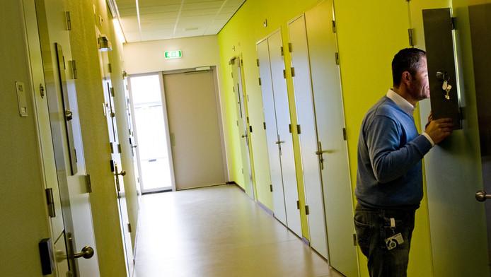 Een medewerker in GGZ-instelling de Woenselse Poort in Eindhoven opent het kijkluik in een kamerdeur.