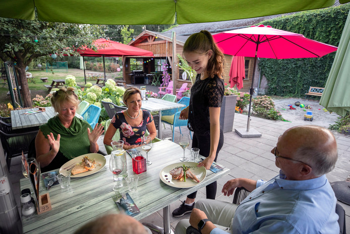 Intieme hoekjes met houten tafels en banken tussen het groen bieden privacy in de tuin van Tuincafé De Witte Zwaan.