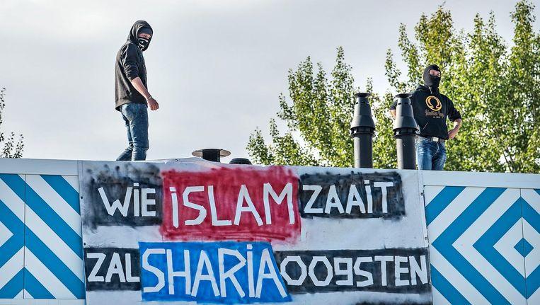 Twee mannen met bivakmutsen op van de extreem-rechtse actiegroep Identitair Verzet plaatsten maandagochtend een spandoek op het dak van de islamitische middelbare school Cornelius Haga Lyceum in Amsterdam Beeld Guus Dubbelman / de Volkskrant