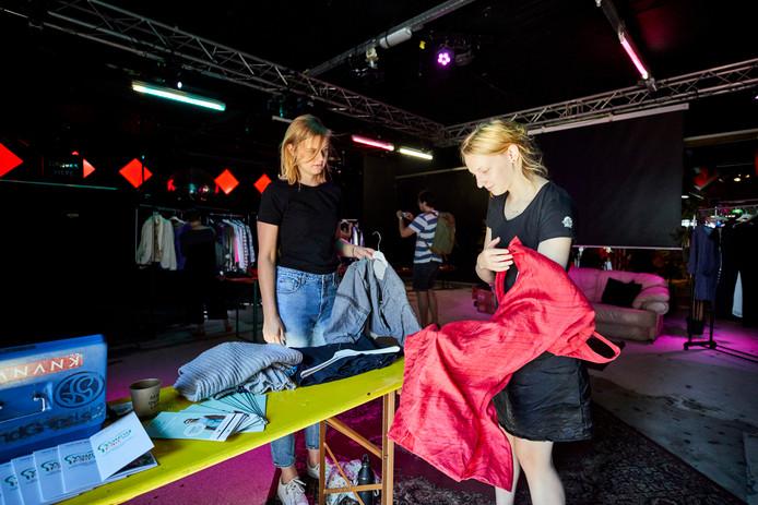 Een bezoeker van het Fair Fashion Festival bekijkt een duurzaam kledingstuk. Volgens Vera Lenting van kledingzaak Natur-el staat duurzaam ook voor goede kwaliteit.