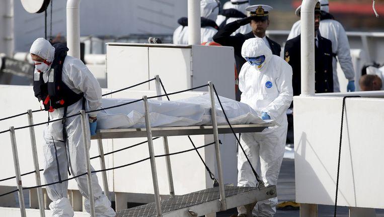 De Italiaanse kustwacht tilt een lichaam in een lijkzak aan wal. Beeld reuters