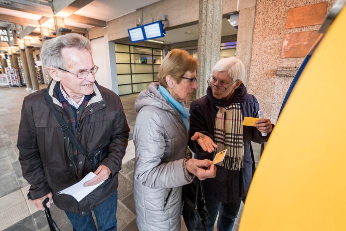 Grietje Koopman (links) legt aan één van de ouderen uit hoe je de OV-chipkaart opwaardeert.