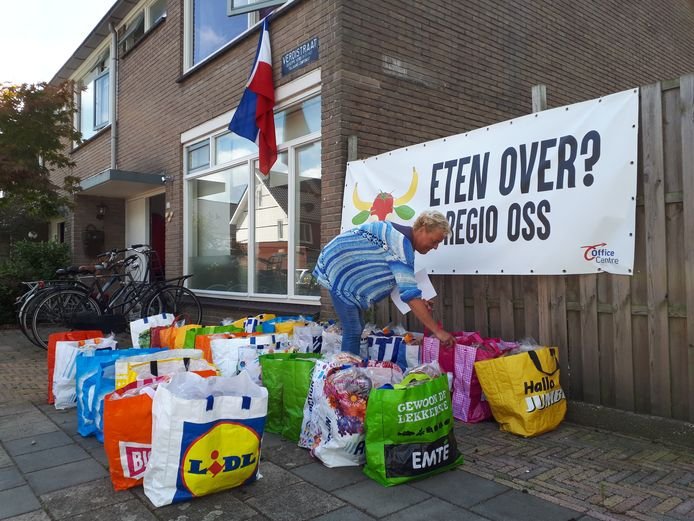 Angelique Maas controleert de tassen met voedsel voor de deur van haar huis.