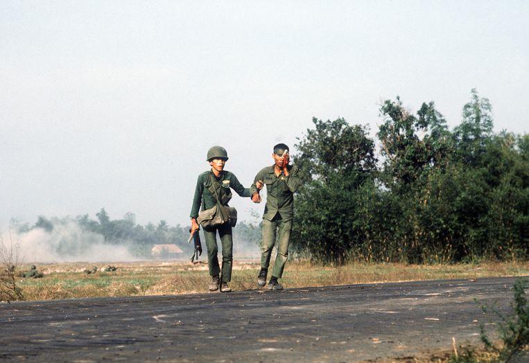 Een Zuid-Vietnamese soldaat begeleidt een gewonde medesoldaat tijdens een operatie in het Trang-Bang-district, vlakbij Saigon, 27 januari 1973. Beeld AFP