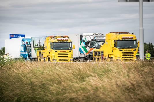 De zwaar beschadigde vrachtwagens op de A15 worden geborgen.