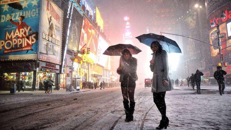 Twee vrouwen wachten op Times Square op een taxi in de sneeuwstorm. Beeld afp