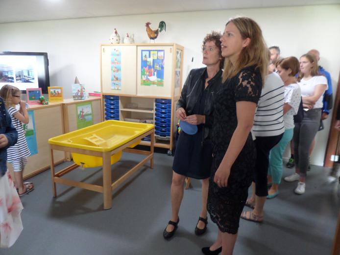 Directeur Hennie Schermers (l) laat Carola Schouten de school zien.