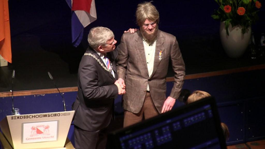 Jelte Sondij met plakbaard werd vrijdag gefeliciteerd met zijn lintje door burgemeester Jan van Zanen.