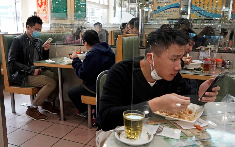 Bezoekers van dit restaurant in Hongkong eten achter plastic schermen om elkaar niet te besmetten met het coronavirus. Beeld Kin Cheung / AP