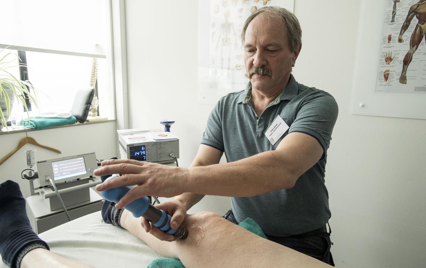 Andre Stroet, shockwavetherapeut bij praktijk Fyrtuoos, waar hij shockwave-therapie toepast op de knie van Borculoër Gerard Pragt.