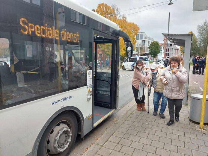 Een van de bewoners wordt de bus op geholpen. Zij werden opgevangen in sporthal Bourgoyen even verderop.