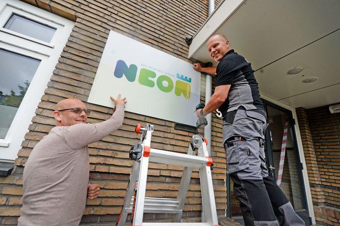 De nieuwe naam van het Corylus College wordt op de muur geschroefd: Neon College. Dave Attema (l) en Michel Siegersma hangen het bord op.