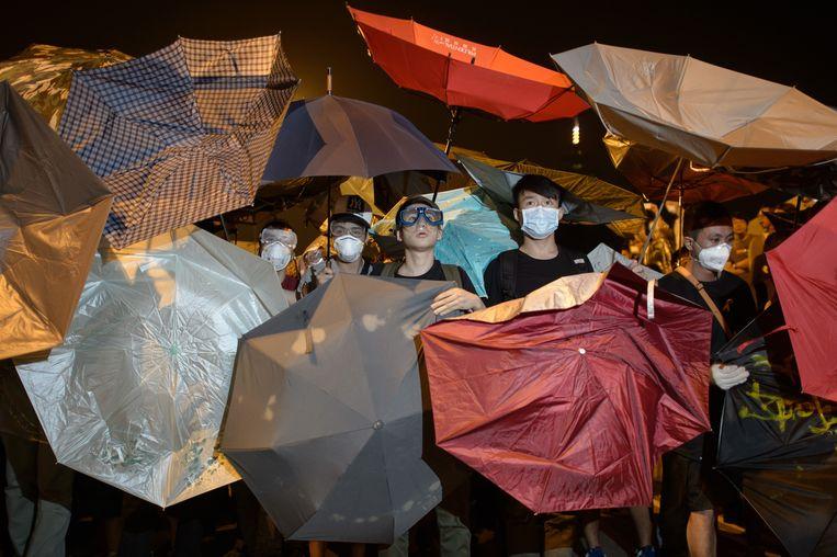Demonstranten kijken in de richting van de politie die op hen afkomt, vlakbij het overheidscomplex van Hongkong, op woensdag 15 oktober. Beeld afp