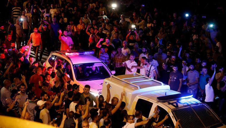 Palestijnse betogers pogen de weg te blokkeren voor Israëlische politiewagens. Beeld afp