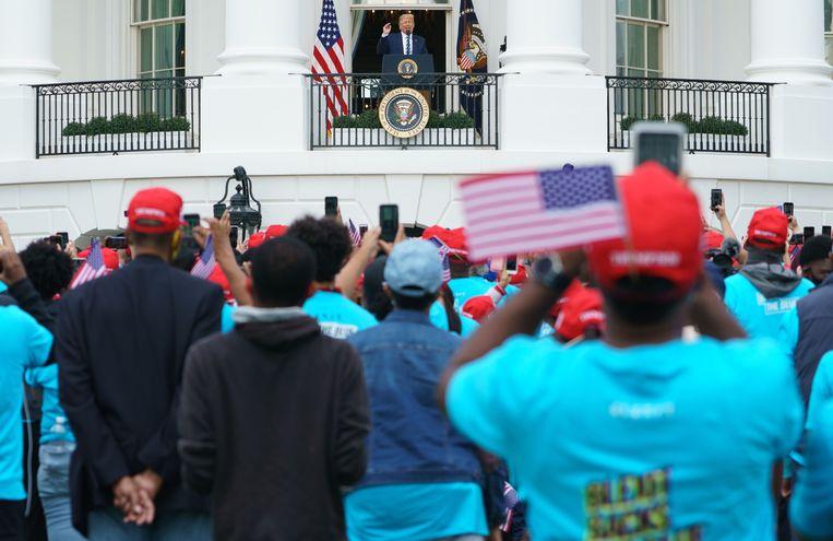 Trump houdt voor het eerst sinds hij positief werd getest op het coronavirus weer een toespraak, afgelopen zaterdag vanuit het Witte Huis in Washington DC. Hij wil snel weer gaan campagnevoeren, de presidentsverkiezingen zijn over drie weken. Beeld AFP