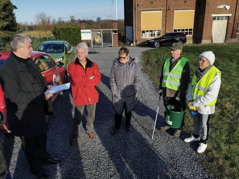 Schepen van Afvalbeleid Johan Servé (Sp.a) geeft aan enkele zwerfvuilvrijwilligers uitleg over de harde aanpak van sluikstorters in Halle.