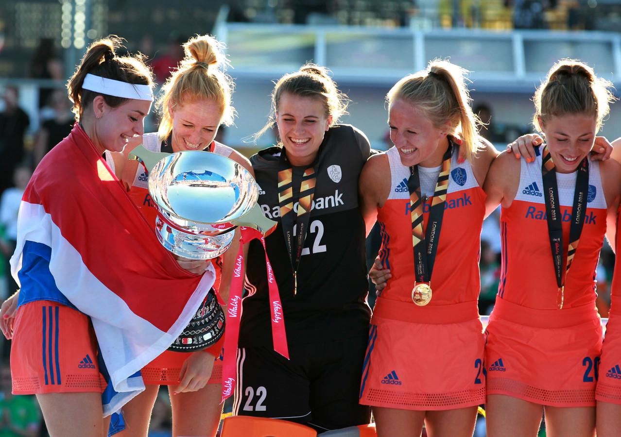 De Nederlandse hockeyvrouwen kijken stralend naar de wereldbeker.
