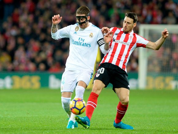 Real Madrid's Spanish defender Sergio Ramos (L) challenges Athletic Bilbao's Spanish forward Aritz Aduriz during the Spanish league football match Athletic Club Bilbao vs Real Madrid CF at the San Mames stadium in Bilbao on December 2, 2017.  / AFP PHOTO / ANDER GILLENEA