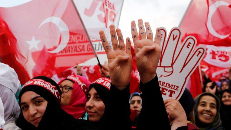 Aanhangers van Turkse president Erdogan tonen hun handen met daarop 'Ja' geschreven tijdens een campagnebijeenkomst voor het referendum in Istanbul. Beeld reuters