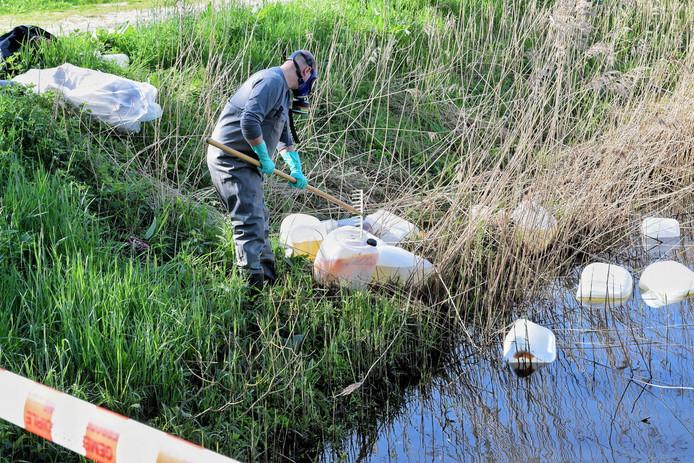 De vaten die gedumpt zijn in de sloot aan het Boterpad in Goirle worden uit het water gevist.