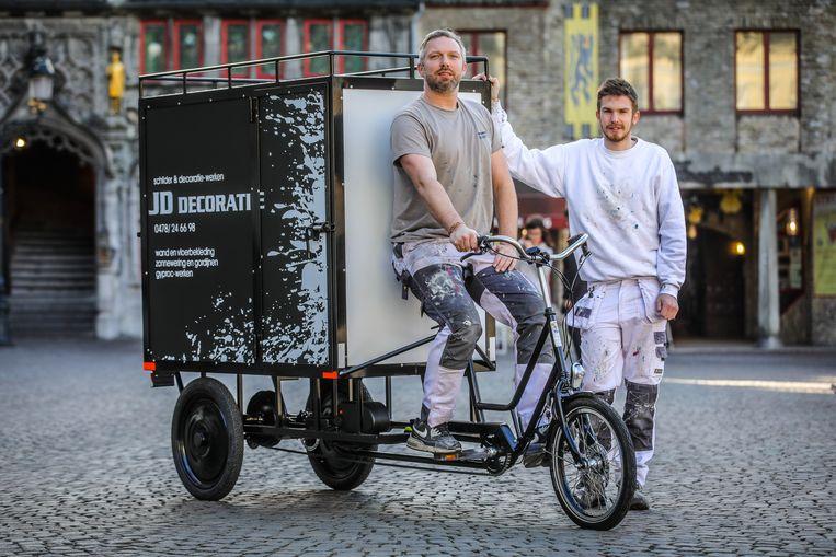 Schilders Jimmy Desmet en Kevin Demuyt rijden met deze cargofiets door de stad.