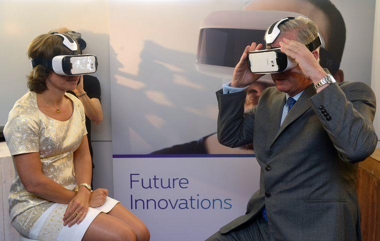 De Belgische koning Filip zet tijdens een bezoek aan het telecombedrijf Proximus in 2015 samen met ceo Dominique Leroy een virtual-realitybril op. Beeld Getty