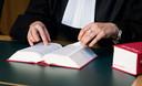 Een rechter met wetboek in de rechtszaal.