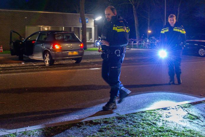 Politie in kogelwerende vesten op zoek naar sporen, na de schietpartij begin deze maand bij sporthal Mheenpark. Op de achtergrond de beschoten auto.