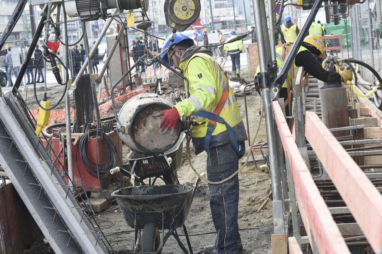 Honderden bouwvakkers werken de klok rond aan hun arbeidsintensieve taak.
