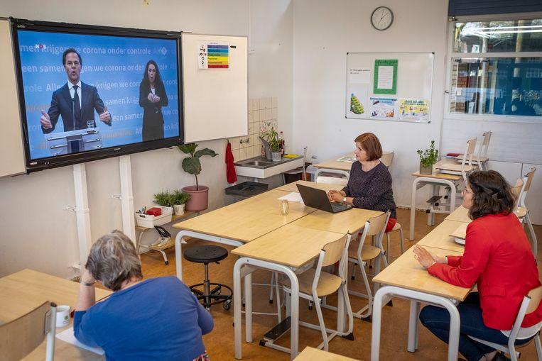 Op basisschool De Windroos in Zaandam kijkt directeur Bernadette von den Benken (midden) met collega's Trix Groenewold (links) en Suheda Sarikya dinsdag naar de persconferentie van premier Rutte over de coronacrisis. Beeld Patrick Post