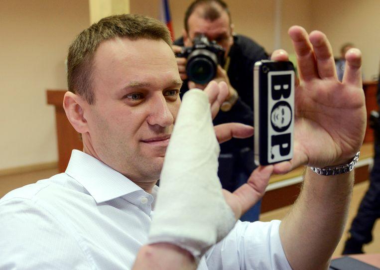De Russische oppositiepoliticus Alexei Navalny neemt een foto met zijn smartphone.  Beeld AP