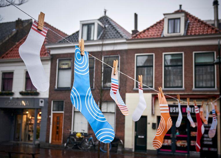 In Delft hangen waslijnen met sokken om aan te geven dat burgers meer moeten doen om wateroverlast tegen te gaan.  Beeld Phil Nijhuis