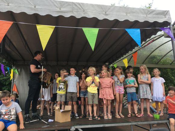 Wim Claeys op een schoolfeest: een hoop kinderen op het podium, en de rest ervoor