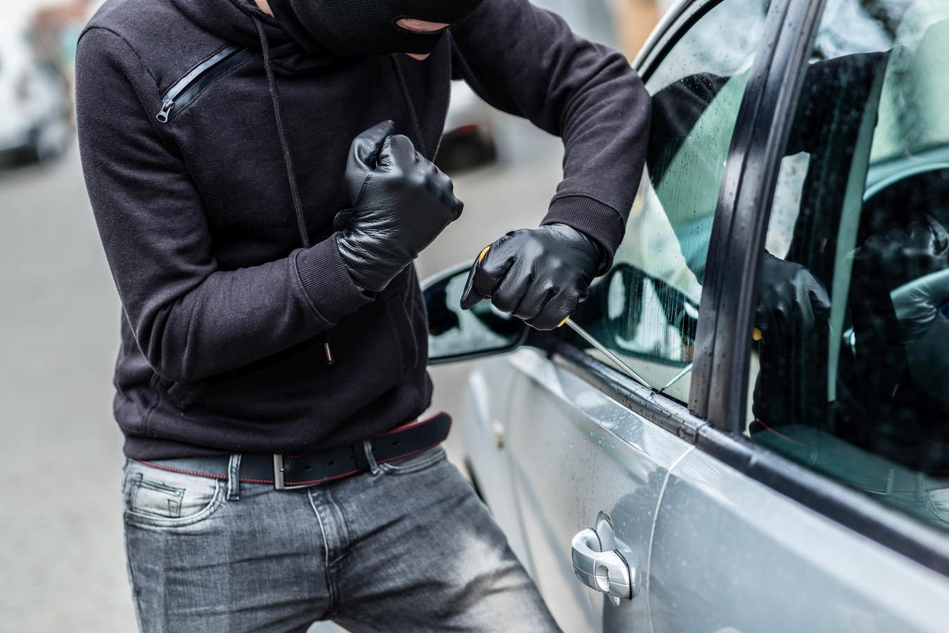 Een inbreker probeert een auto open te maken. (foto ter illustratie)