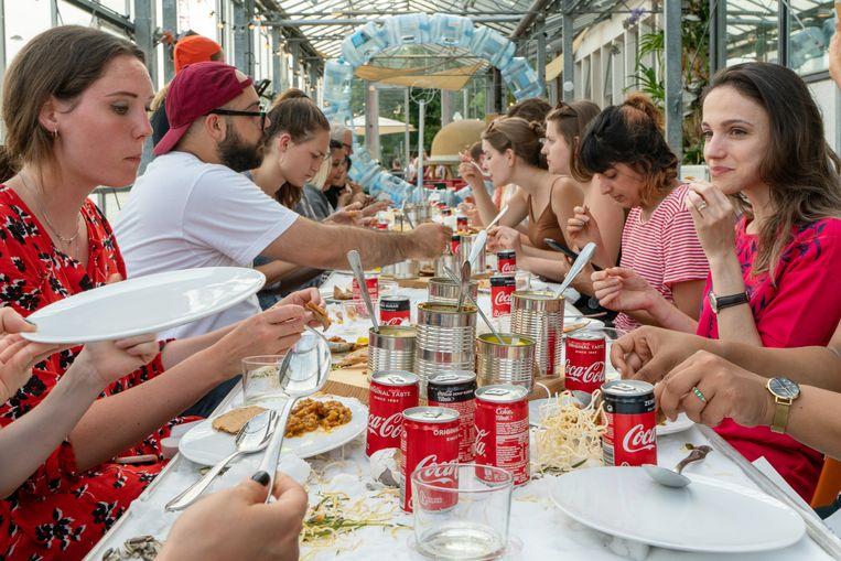 Gasten drinken cola ('goedkoper dan water') tijdens het Neo Futurist Dinner in Mediamatic. Beeld Sjoerd Houben/Mediamatic