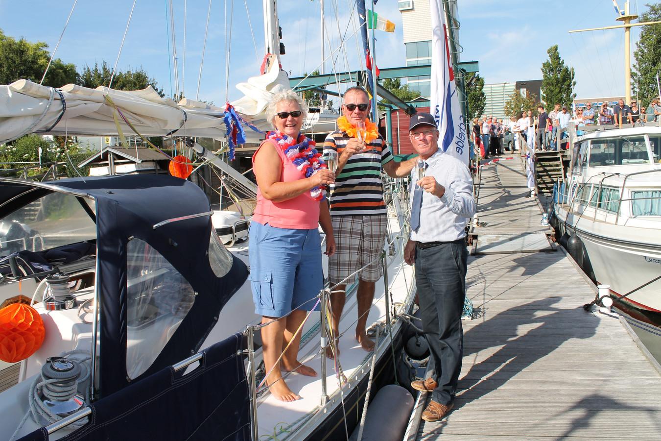 De havenmeester (voorgrond), familie en vrienden (achtergrond) verwelkomen de zeezeilers.