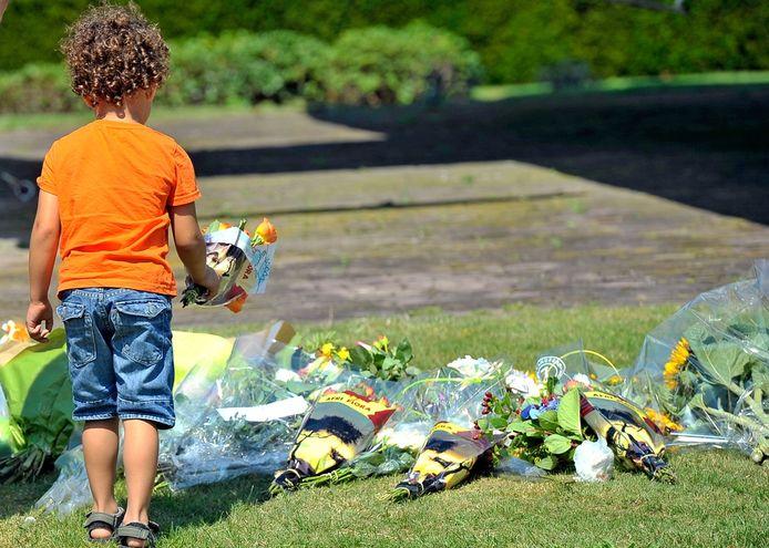 Een kind legt bloemen bij de ingang van vliegbasis Eindhoven.
