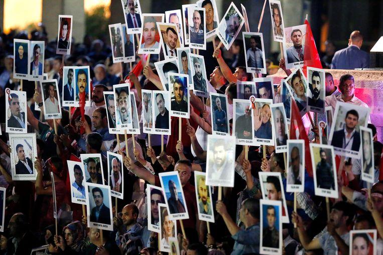 Voor het parlementsgebouw in Ankara tonen betogers foto's van de 250 slachtoffers van de coup. Het afgelopen jaar verloren ook meer dan 150.000 mensen hun baan. Beeld EPA