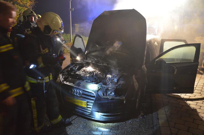 De brandweer is bezig met het blussen van de auto.