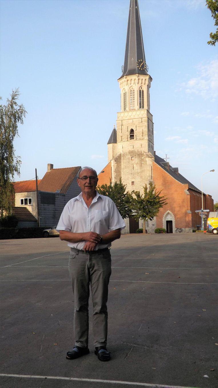 Raymond Claes, regisseur van het Schevetorenfeest, op het kerkplein, met op de achtergrond de 'scheve toren' van Schelle.