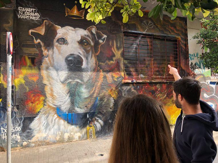 Gids Nikos Tongas wijst op een muurschildering in Athene. Beeld Thijs Kettenis
