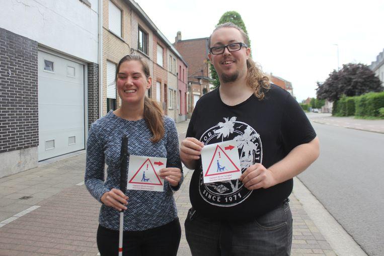 Brenda Vanvoorden en Dylan Lanckman met hun sticker die waarschuwt voor blinde passagiers.