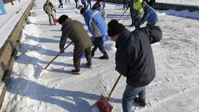 Baanvegers werken op 6 januari op de ijsvloer van de Luts, een van de knelpunten van de Elfstedentocht. Beeld ANP
