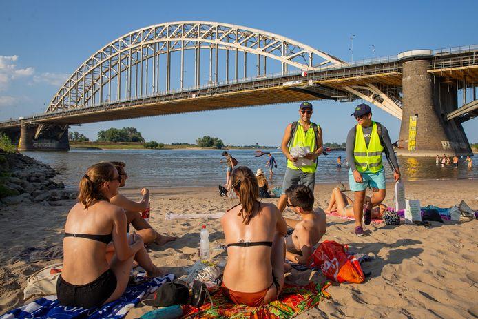 'Afvalcoaches' Joost van Kampen (l) en Zenon Croes (r) delen namens de Dar afvalzakjes uit aan bezoekers van de stranden onder de Nijmeegse Waalbrug.