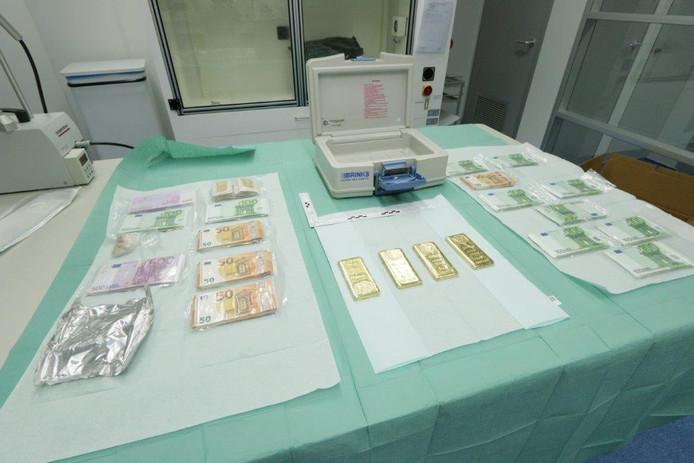 Bij huiszoekingen heeft de politie voor een half miljoen euro aan cash en goudstaven in beslag genomen.