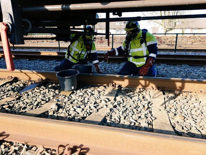 Incidentbestrijders van ProRail onder de trein.
