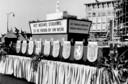 De optocht 'Hengelo Herrezen' in 1958. Twentse gemeenten feliciteerden Hengelo met een eigen praalwagen. Op de achtergrond de Telgenflat.