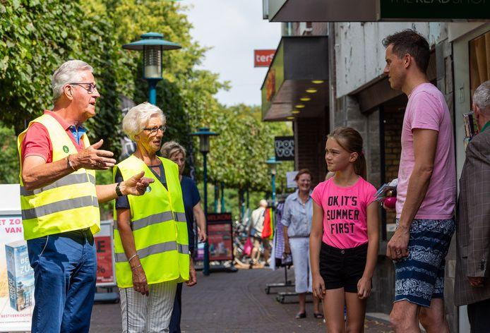 Freek Vos en Riet Bosch helpen als vrijwilligers om de coronamaatregelen in het centrum van Epe te verduidelijken. Hier zijn ze in gesprek met de familie Drost uit het Brabantse Baarle-Nassau.