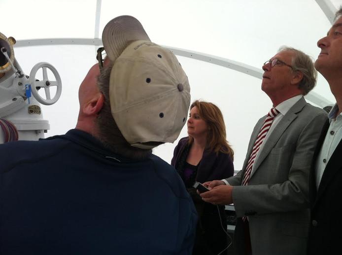 Burgemeester van Bernheze Marieke Moorman en gedeputeerde Yves de Boer bekijken de zonnetelescoop. Patrick Duis (links) geeft uitleg.