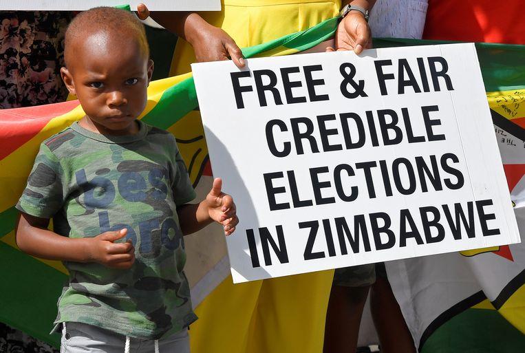 Een jonge 'demonstrant' bij de Zimbabwaanse ambassade in Londen op 4 augustus Beeld REUTERS